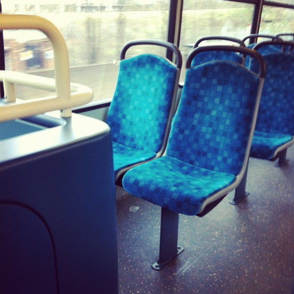 A photo showing two seats directly behind the stairs on the upper level of a double decker bus in London