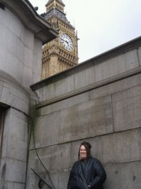 Me, wearing a leather jacket with my hair in an up-do, smiling beneath Big Ben in London, UK